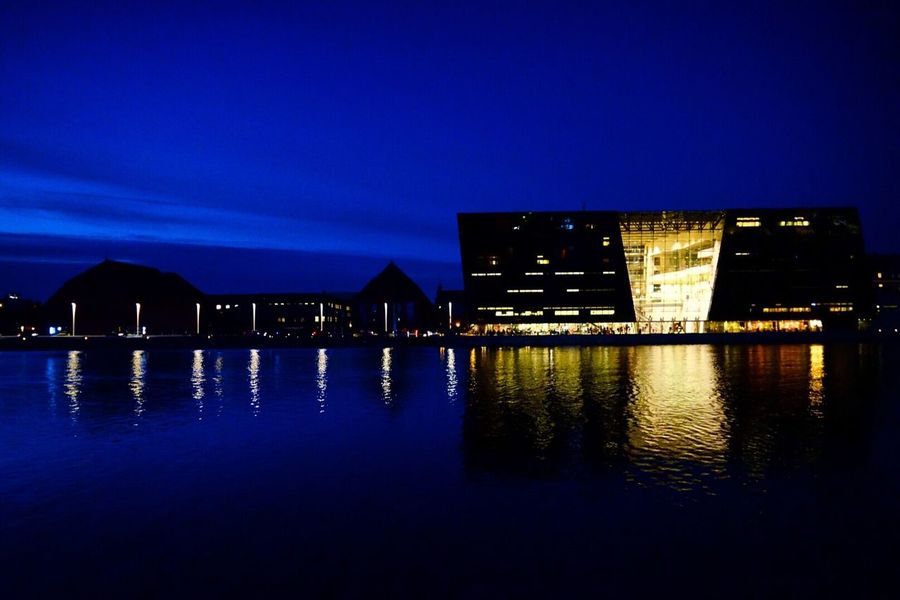 Reflection Built Structure Architecture Building Exterior Waterfront Blue Water Sky Night Illuminated Illumination City No People Nature Outdoors Copenhagen Denmark Adapted To The City By The Canal Cityscape City Life Sea Warm Atmosphere Sunset Warm Colors