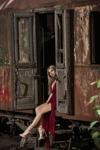 Portrait woman sitting on abandoned train doorway