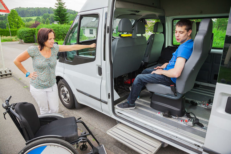 Man sitting in van while woman standing by wheelchair on road