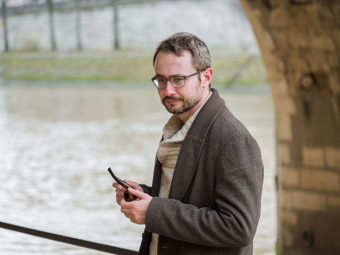 Man holding mobile phone while standing against lake
