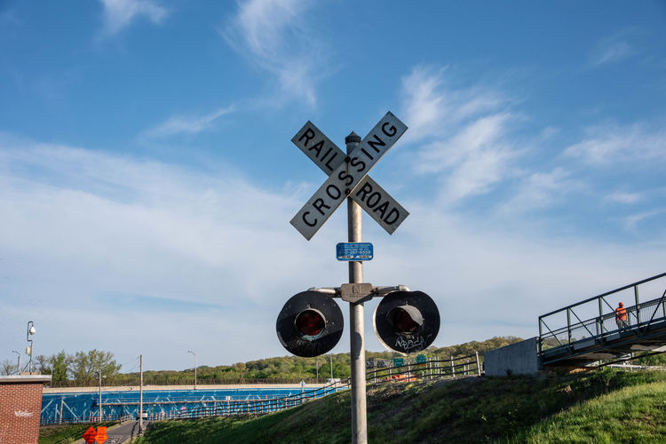 Railroad crossing sign on field against blue sky