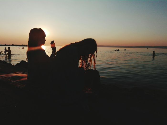 Friends sitting on pier during sunset