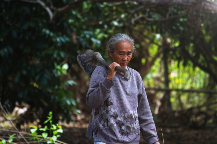 Old woman farmer holding a hoe while walking International Women's Day 2019 One Person Tree Standing Day Lifestyles Outdoors Innocence Nature Portrait Plant Front View Asian  Old Woman Female Nature Lights Morning Rays Of Light Hoe Tired Back Home Farm Garden Rest Mother