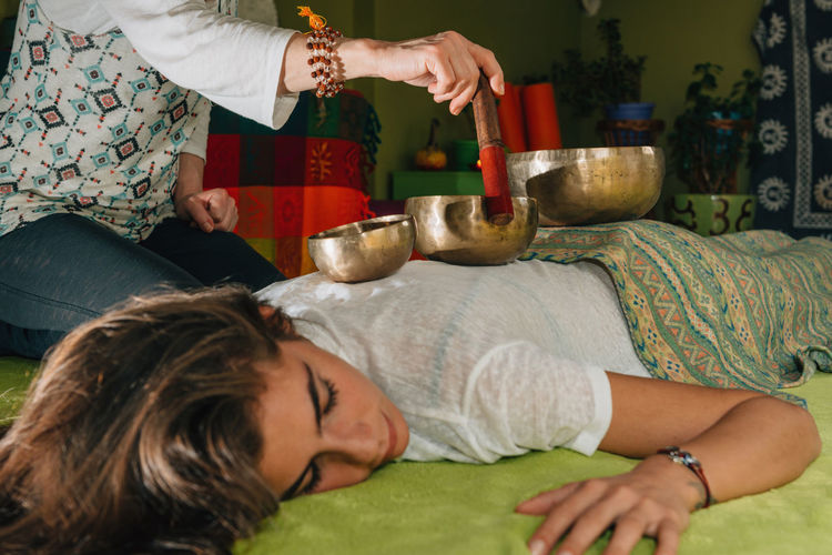 Midsection Of Therapist Playing Rin Gong On Young Woman At Spa