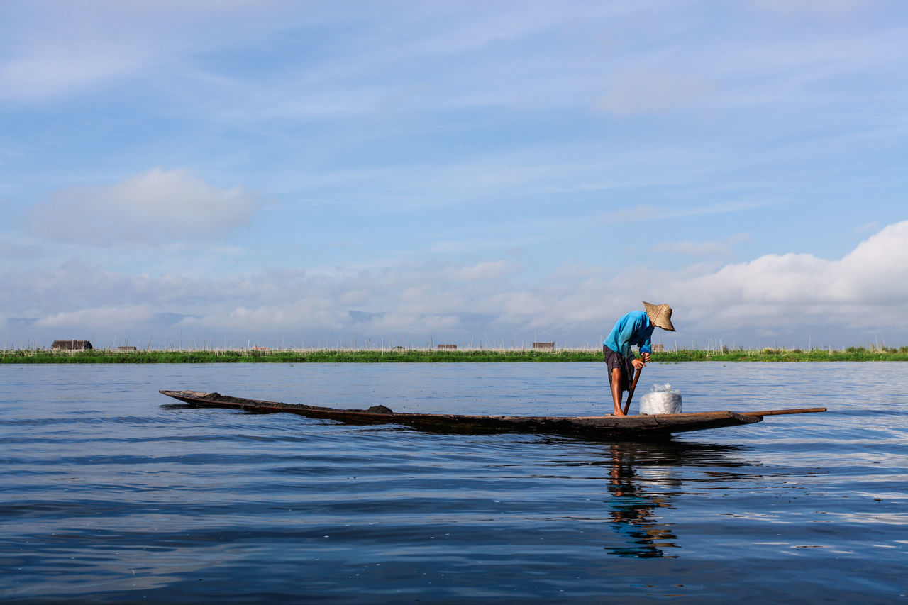 Scenic View Of Man Standing On Canoe