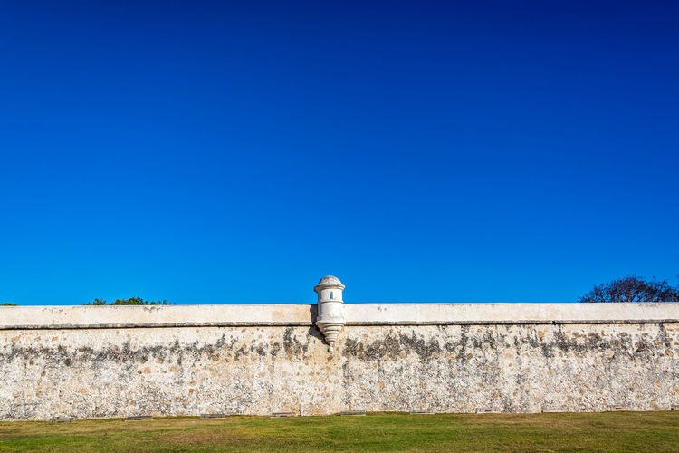 Defensive wall against clear blue sky during sunny day