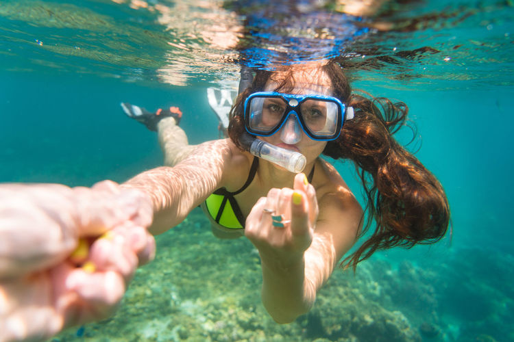 Portrait of young woman snorkelling in sea with her partner