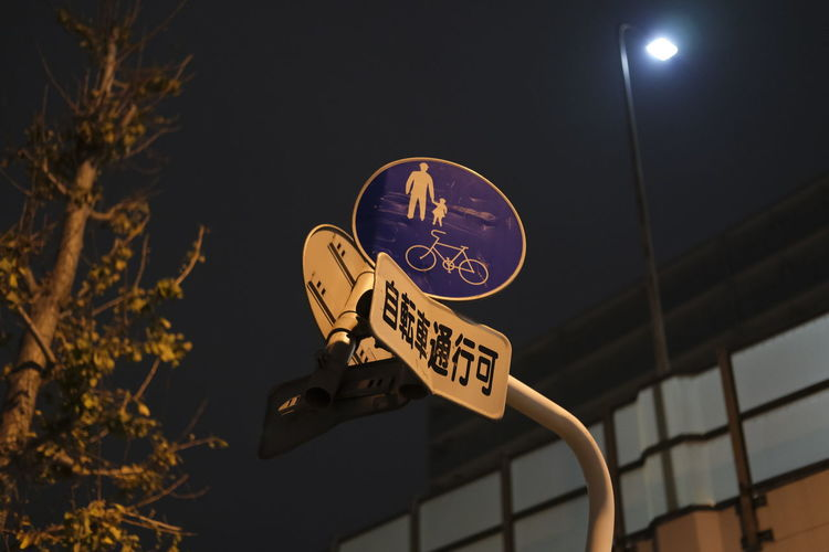 Low angle view of road sign against sky at night