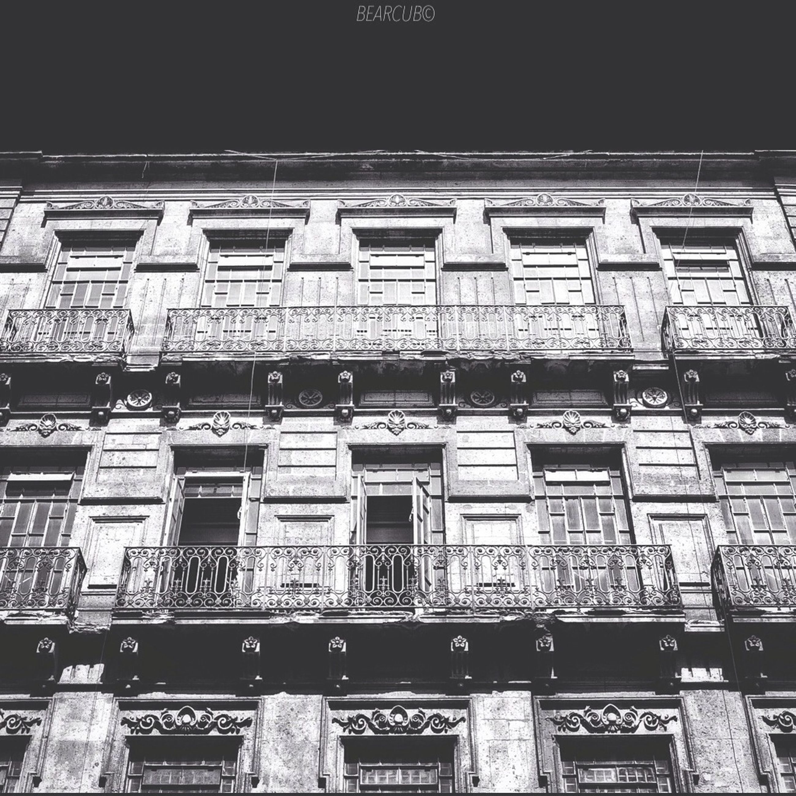 architecture, built structure, building exterior, low angle view, text, window, western script, building, facade, city, outdoors, in a row, side by side, no people, day, communication, repetition, architectural feature, art and craft, non-western script