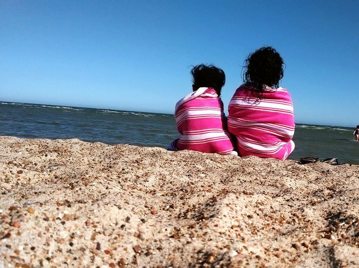 Rear View Of Girls Wrapped In Towel Sitting On Shore Against Clear Blue Sky