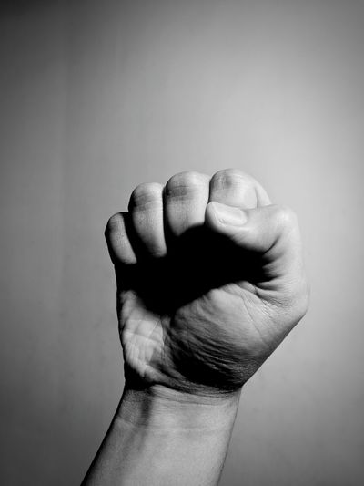 Close-up of fist against gray background