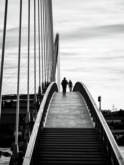 Rear View Of People Walking On Steps Against Sky