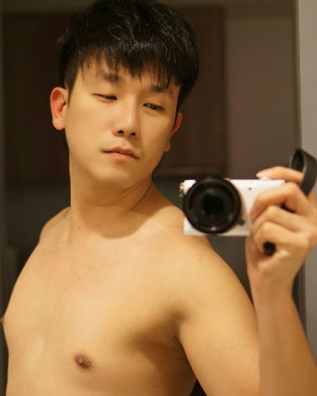 Shirtless mid adult man taking selfie with camera reflecting on mirror at home