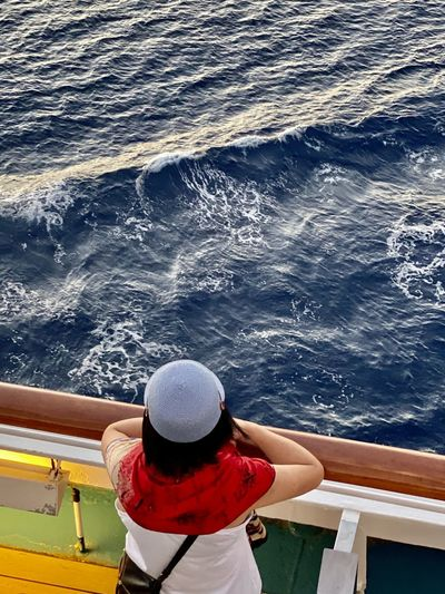 Rear view of woman standing by railing of boat in sea