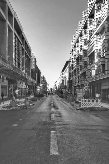 Empty road amidst buildings in city against clear sky