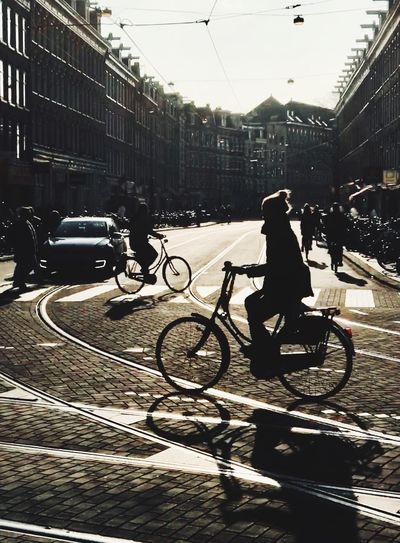 People riding bicycle on city street amidst buildings