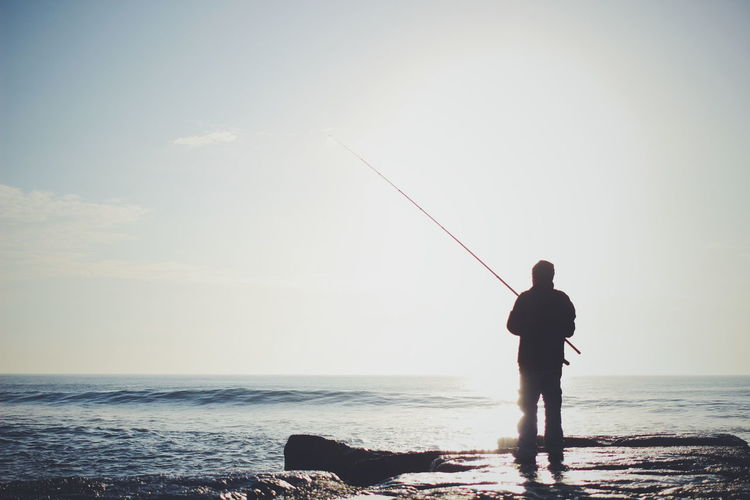 Rear view of man fishing in sea against sky on sunny day