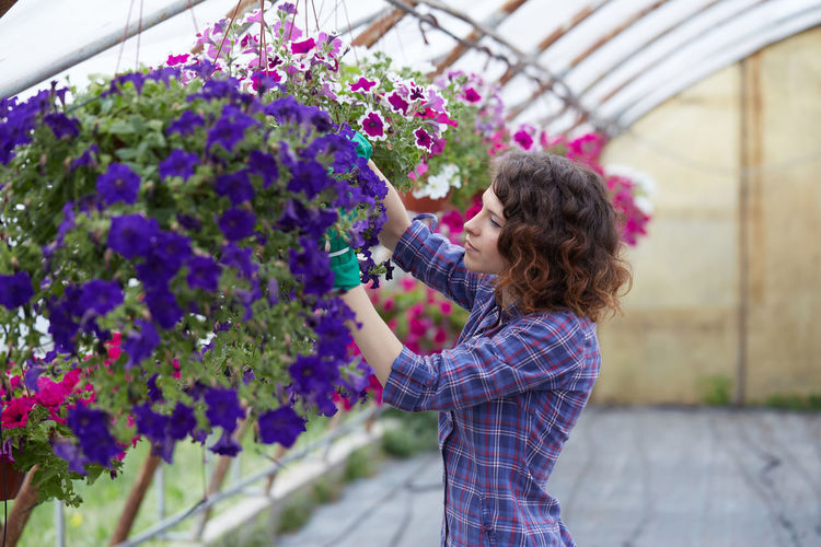 Side view of woman examining flowers in greenhouse