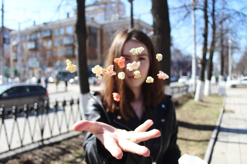 Portrait of woman throwing popcorn while standing in city