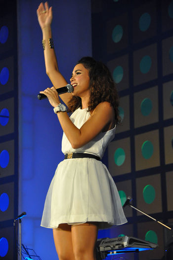 Young woman with arms raised standing at music concert
