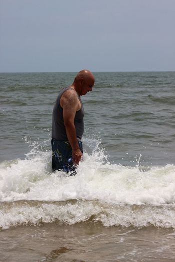 Side View Of Man Standing In Sea Against Clear Sky During Sunny Day