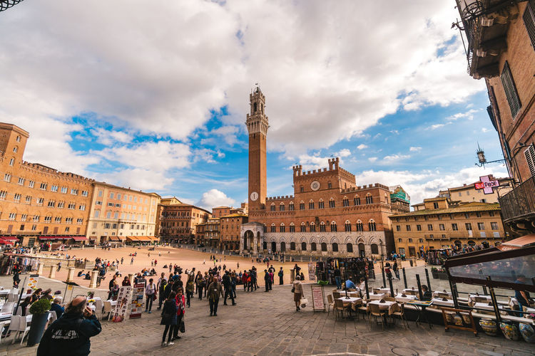 Siena, Italy - November 2, 2016: View of the magnificent square of the field with the famous tower called Mangia. Architectural Architecture Bell Tower Brick Building City Europe Façade Gothic Historic Historical Italian Italy Landmark Mangia Medieval Old Palio People Piazza Del Campo Renaissance Siena Square Square Of Field Torre Del Mangia Tower Town Travel Tuscany Vintage