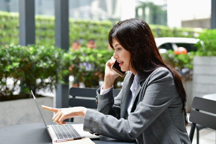 Adult Business Business Person Businesswoman Communication Computer Connection Focus On Foreground Laptop Occupation One Person Outdoors Real People Sitting Table Technology Using Laptop Wireless Technology Women Young Adult