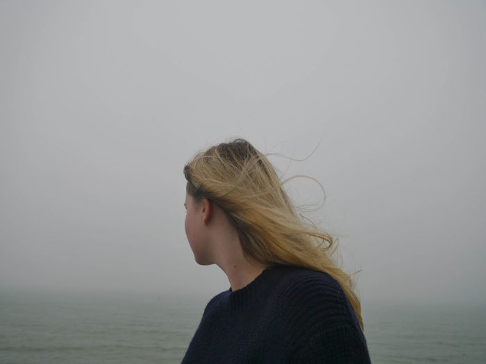 Side view of woman against sky during foggy weather