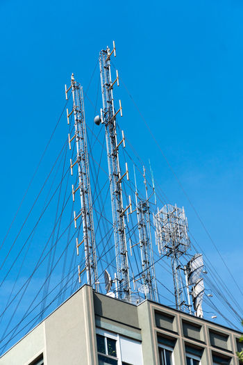 Low angle view of telephone pole against building against clear blue sky
