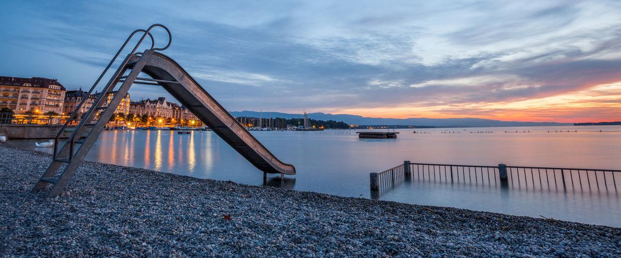 Slide At Lakeshore Against Sky During Sunset
