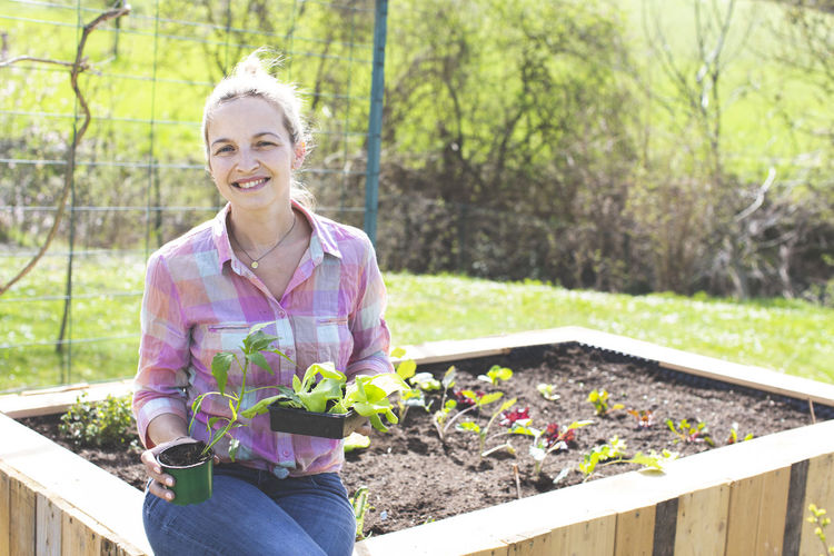 Smiling Woman Sitting On Raised Bed In Yard