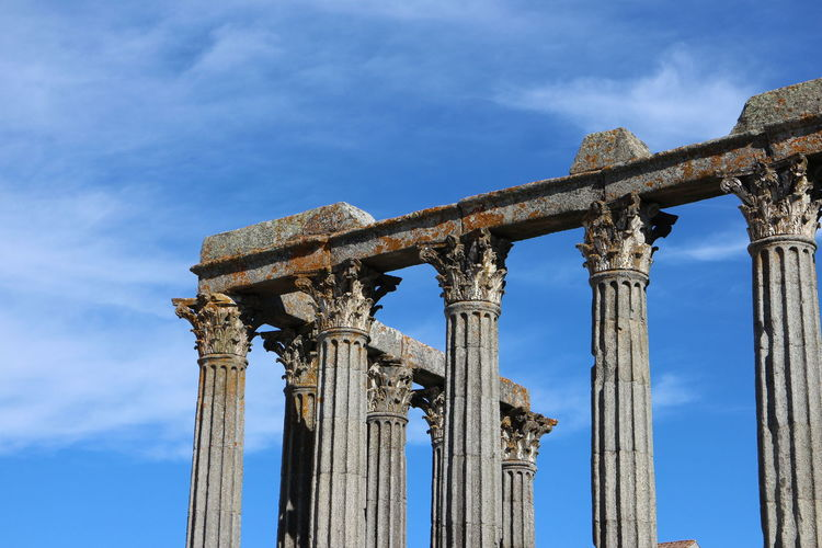 Low angle view of columns at roman temple of evora against sky
