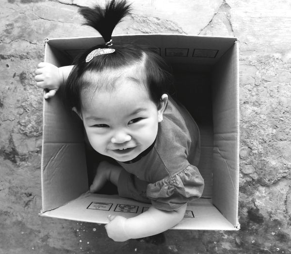 High angle portrait of cute baby girl sitting in cardboard box