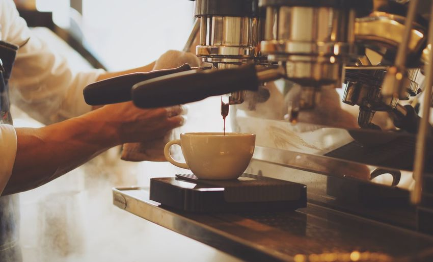 Close-up of man pouring coffee in cafe