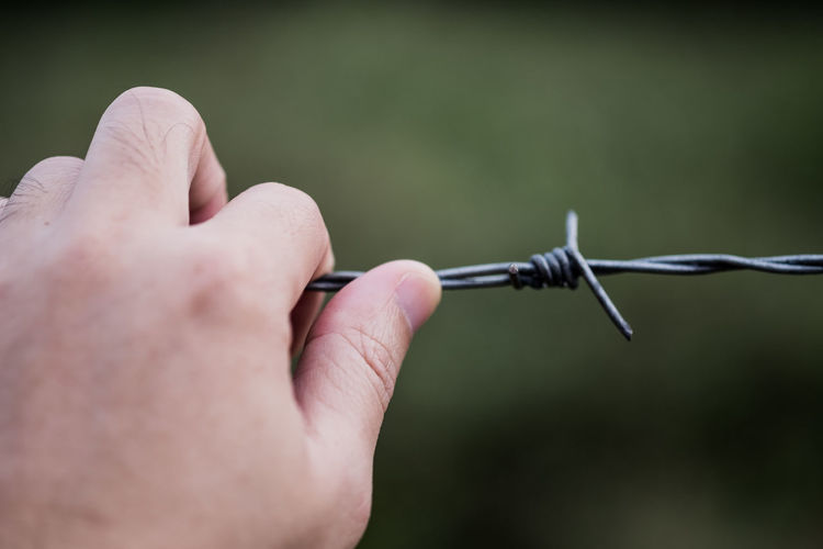 Cropped hand holding barbed wire fence
