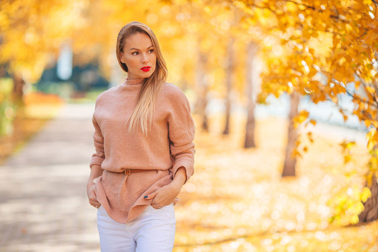 Portrait of woman standing against tree during autumn