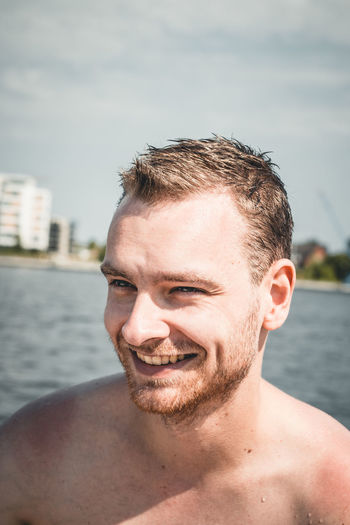 Smiling shirtless man looking away against sea during sunny day