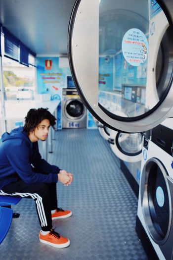 Blue Laundry Washing Machine Washing One Person Full Length Real People Casual Clothing Indoors  Lifestyles Women Sitting Side View Adult Young Adult Looking