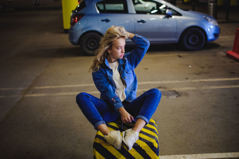 Blond Hair Car Casual Clothing Childhood Day Full Length Happiness Land Vehicle Leisure Activity Lifestyles One Person Outdoors Real People Sitting Transportation Young Adult Young Women