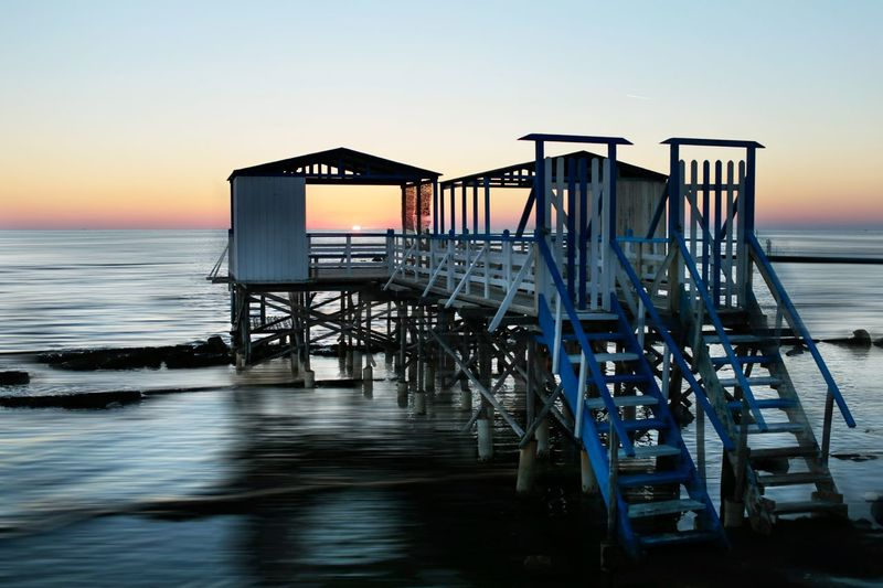 Pier over sea against clear sky during sunset