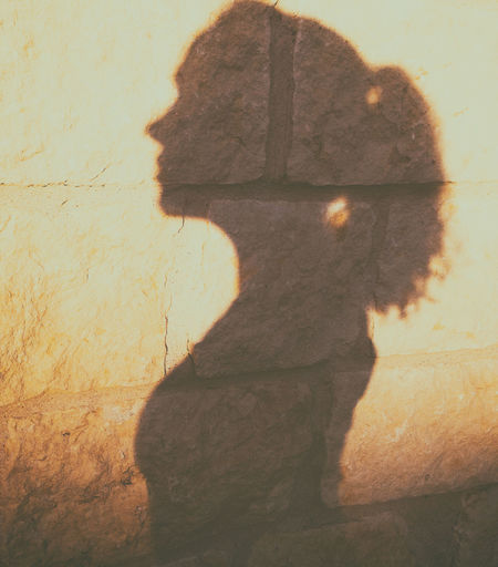 Close-up portrait of woman standing against wall