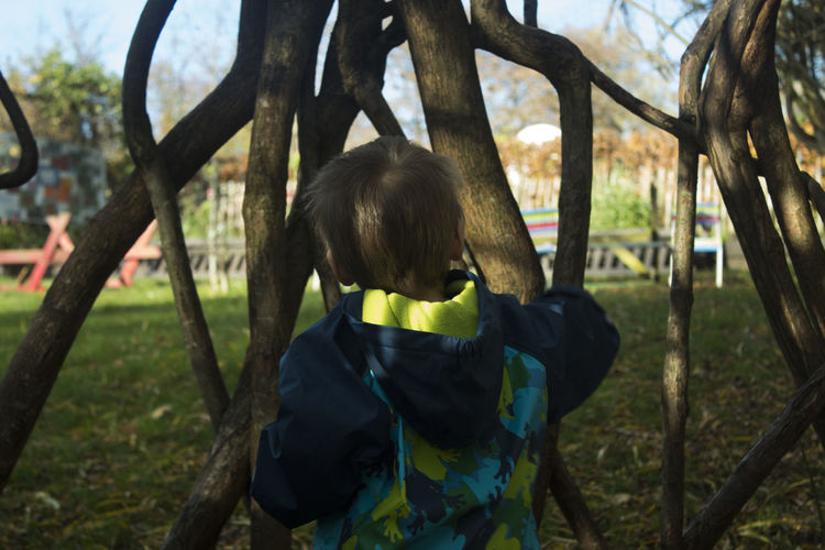 Rear view of boy standing by branches at park