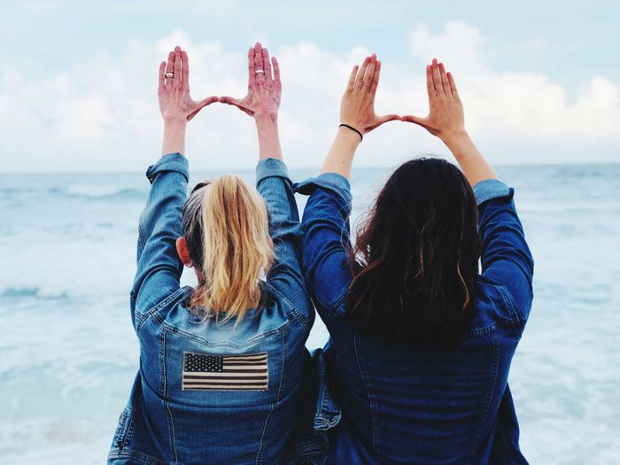Rear View Of Female Friends Gesturing At Beach