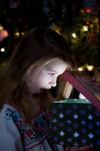 Surprised girl looking into christmas present at night
