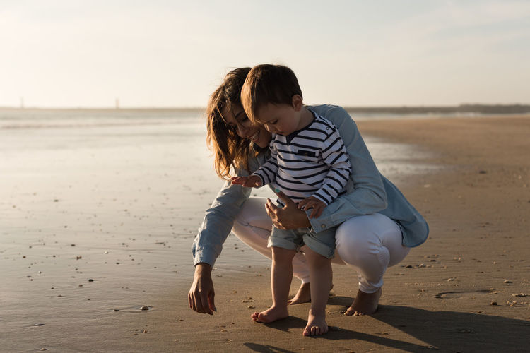 Young mother playing with her little son at he beach Baby Exploring K Latin Mother Woman Beach Hispanic Little Ocean Playing Sand Sky Smiling Son Sunset Toddler  Water
