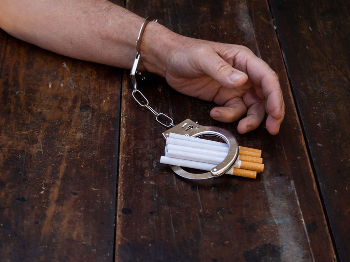 High angle view of man holding cigarette on table