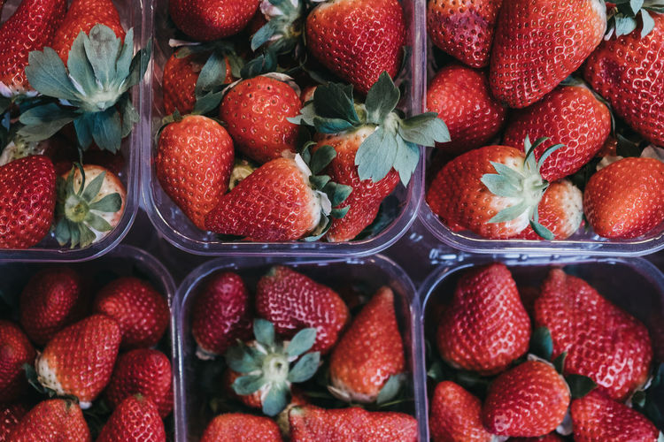 Top view of fresh strawberries on sale, portioned in plastic boxes, on top of a wooden table.