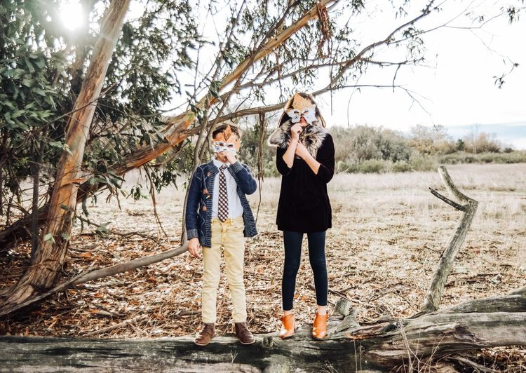 Portrait of siblings holding maple leaves over face while standing in park during autumn
