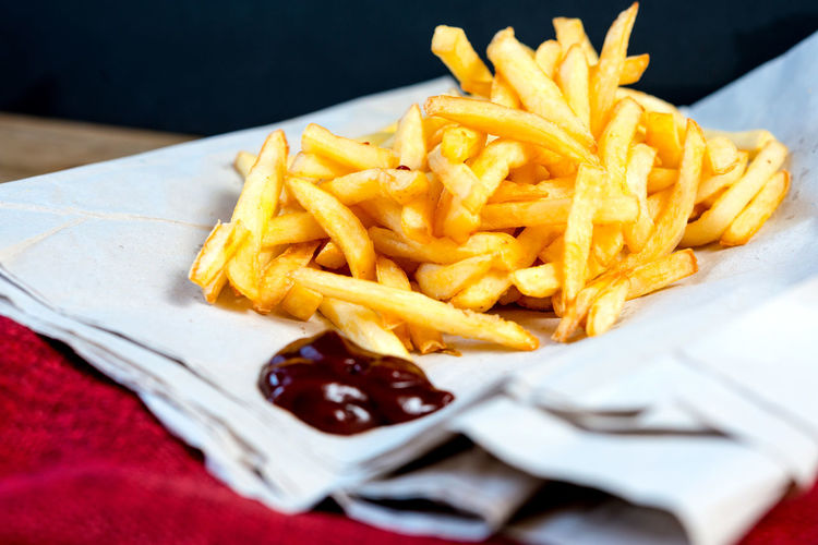 Close-up of fresh french fries served with ketchup on napkin