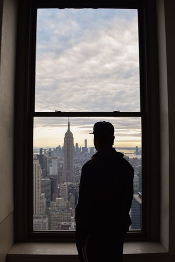 Rear View Of Man Looking At Empire State Building Amidst City Through Window